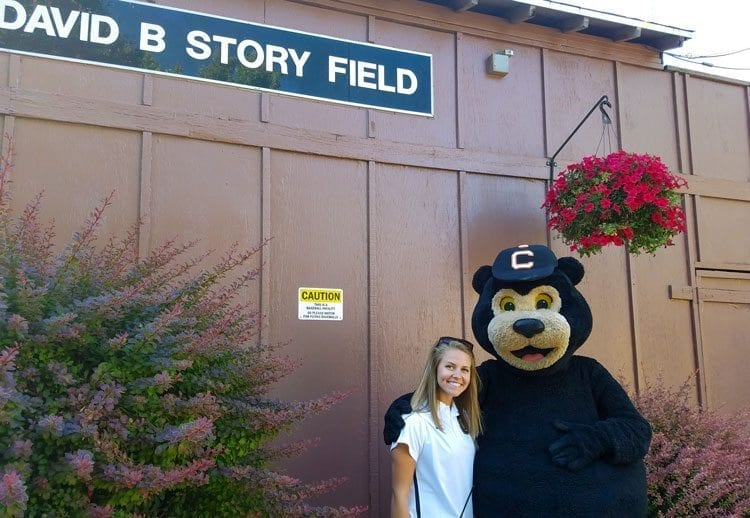 Rachel Moudy, a student at the University of Nebraska Omaha and a La Center resident, hangs out with Corby the Black Bear outside David Story Field during a recent game. Moudy is on schedule to earn a business administration degree next spring and wants a career in sports management. Photo by Paul Valencia.