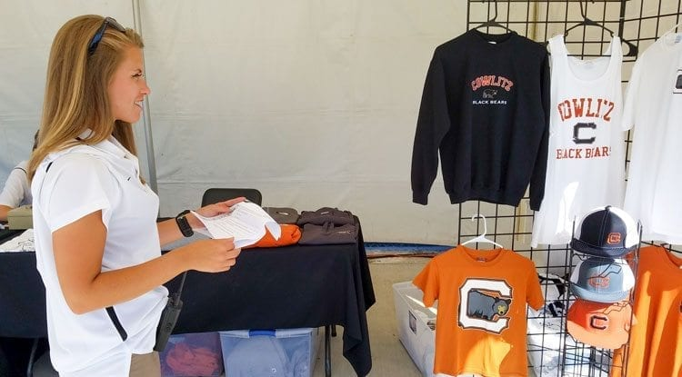"""Rachel Moudy takes a look at her """"script"""" for Sunday's in-game activities, stopping for a minute at the Cowlitz Black Bears merchandise tent. Moudy, 20, is working toward a career in sports management. Photo by Paul Valencia."""
