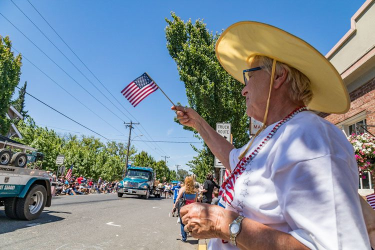 Ridgefield resident Beverly Summerhill is one of many who lined the streets of downtown Ridgefield Tuesday for the annual parade, which serves as the centerpiece for the Ridgefield Fourth of July celebration. Photo by Mike Schultz