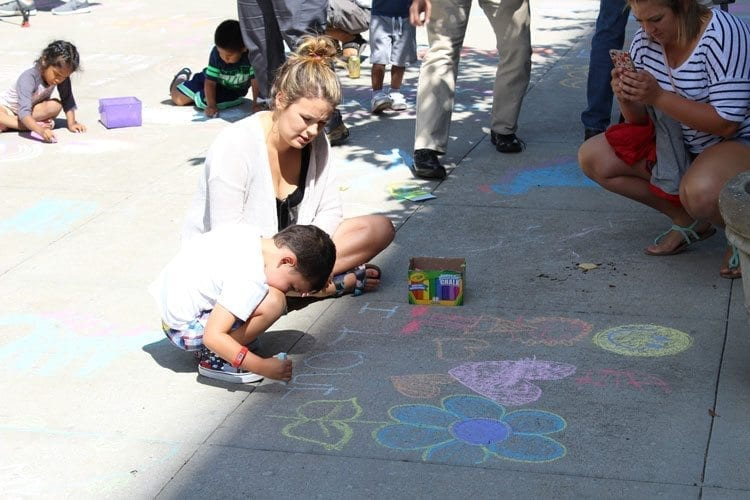 Parents helped their children draw on the sidewalks and joined in the Chalk the Walks event in Vancouver Tuesday. Photo by Alex Peru
