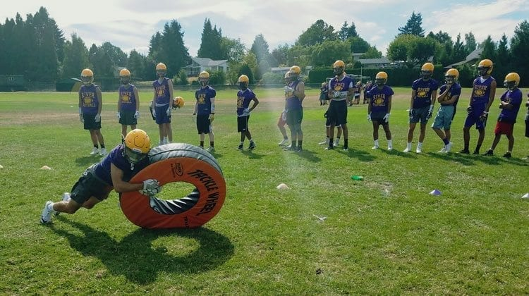 """The Chieftains enjoy taking their turn taking down the """"Tackle Wheel"""" in practice. Photo by Paul Valencia"""