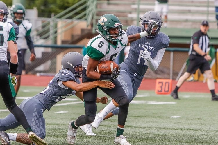 Evergreen receiver Jerontae Burns (5) attempts to elude a Heritage defender in Friday's loss to the Timberwolves. Photo by Mike Schultz