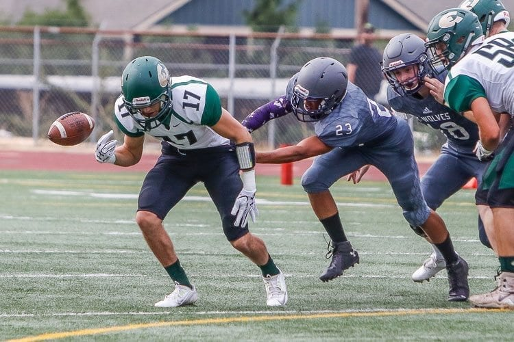 Heritage defender Quobe Altig-Johnson (23) knocks the football loose from Evergreen running back Daniel Moltisanti (17). Photo by Mike Schultz