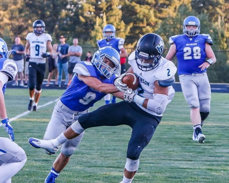Hockinson tight end Jake Beslanowitch tackled by La Center's Evan Honore. Photo by Mike Schultz