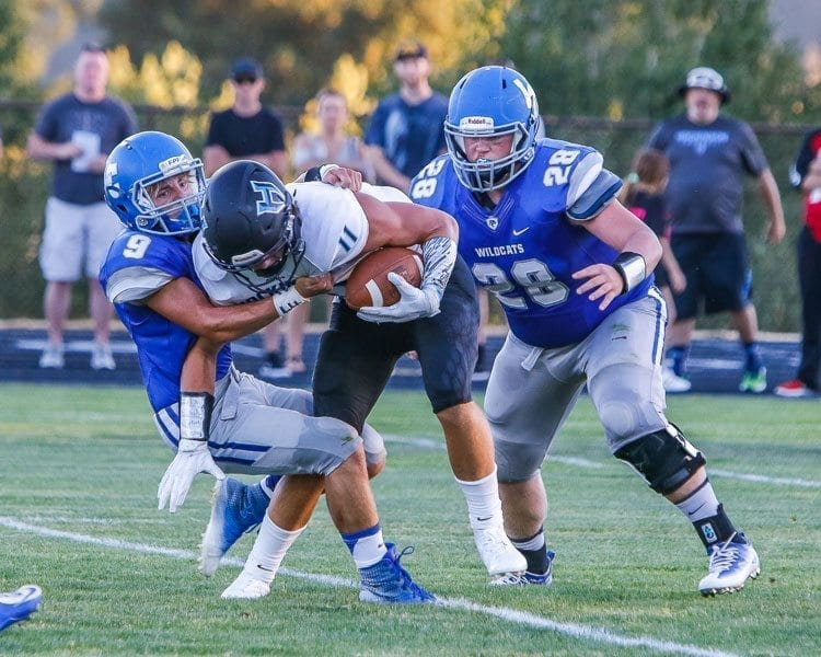 Hockinson wide receiver Sawyer Racanelli tackled by La Center Evan Honore and Colton Dolezal. Photo by Mike Schultz