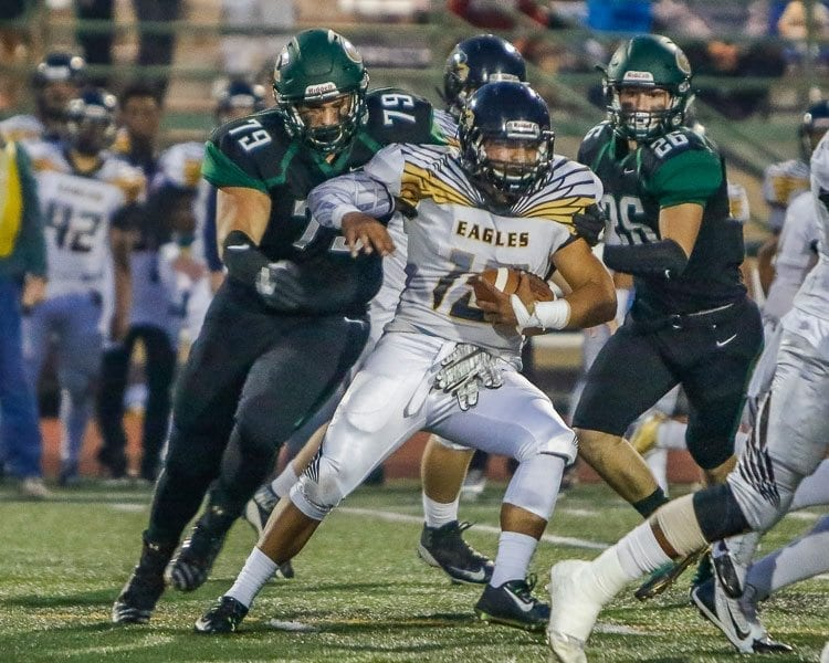 Hudson's Bay running back Akilotoa Kaumatule (15) is swarmed by Evergreen defenders Alex Rodriguez (79) and Jacob Tillman (26). Photo by Mike Schultz
