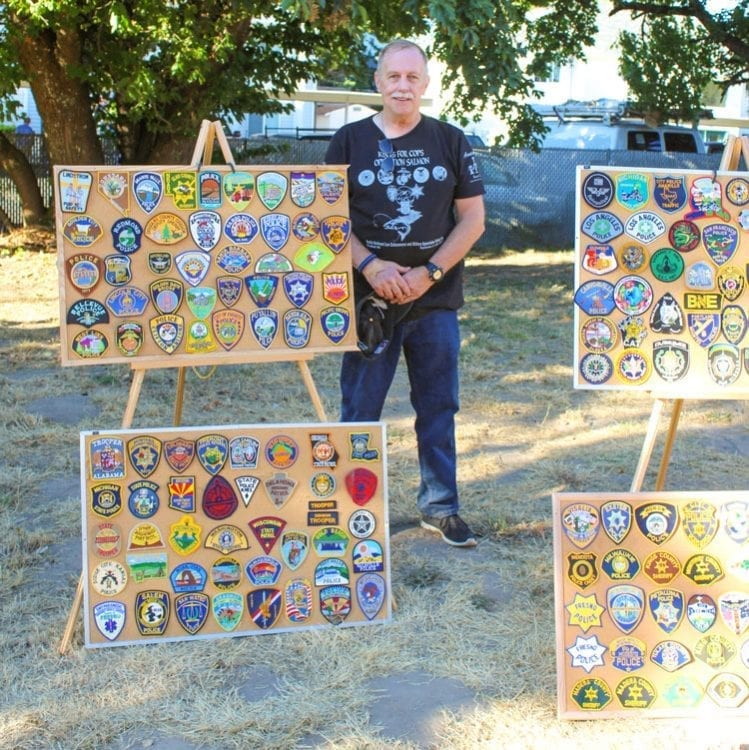 "Retired police officer Steve Allen displayed his collection of law enforcement patches, which he said provided a ""way to get to meet officers from other departments."" Photo by Alex Peru"