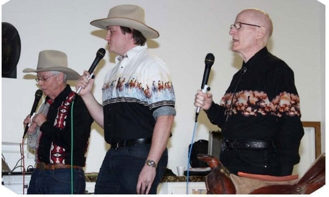 Jim Hattrick, Adam Christman, and Craig Abercrombie (left-to-right) call at a New Year's Eve dance. Photo courtesy of Liza Halpenny