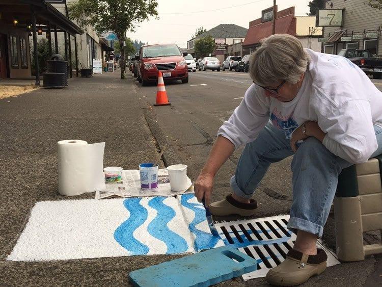 Artist Julie Koch is shown here creating her storm drain art on Battle Ground's Main Street. Photo courtesy of city of Battle Ground.