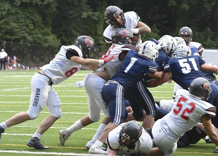 Semisi Schultz jumps over the pile for a first-quarter touchdown for the Camas Papermakers. Photo by Kris Cavin