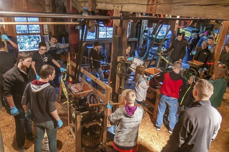 Inside the grist mill, visitors mingled with volunteers to learn about the mill, the cider making process and to even provide hands on help with making the cider itself. Photo by Mike Schultz