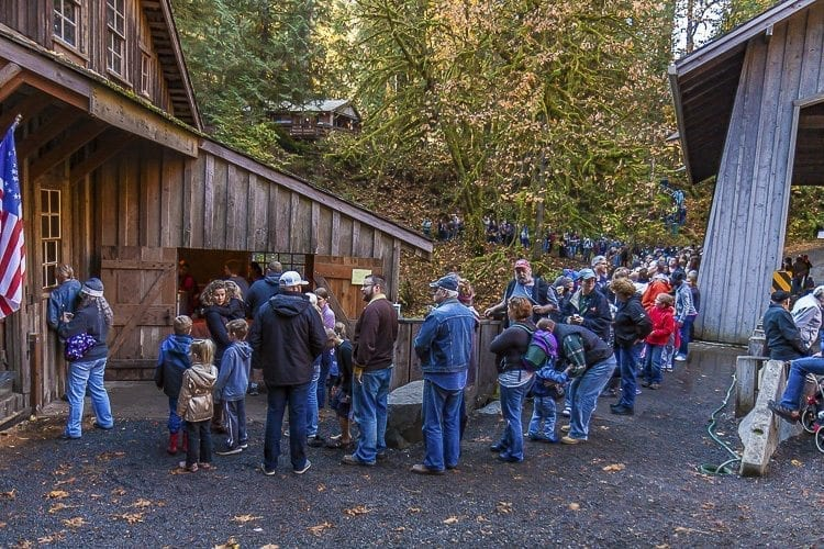 Soon after the first jugs of cider were ready, the line of visitors stretched across the bridge over Cedar Creek and began to line the opposite bank. Photo by Mike Schultz