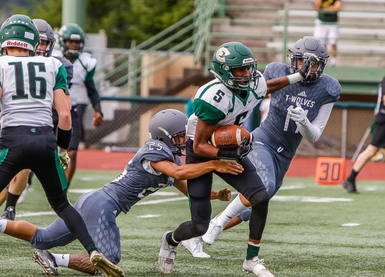 Evergreen needs one win in its final two games to clinch a playoff berth. Here, Jerontae Burns (5) battles for yardage in a game earlier this season against Heritage. Photo by Mike Schultz