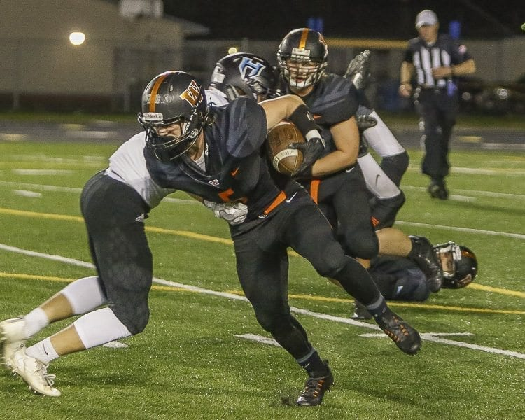 Washougal running back Kade Coons (5) fights for some of his 57 yards rushing in Friday's loss to Hockinson. Photo by Mike Schultz