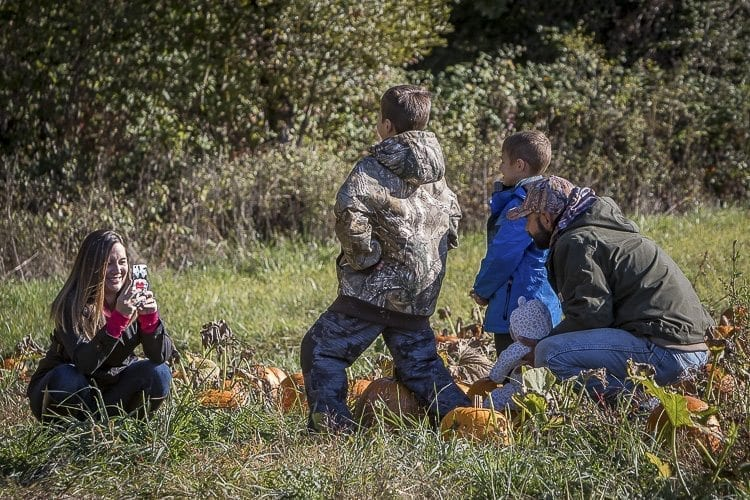 Nicole Meyer takes a photo of Jericho Hanson, Jace Hanson, Alexis Meyer and Andrew Meyer of Battle Ground in the Pomeroy Farm's pumpkin patch. Photo by Mike Schultz