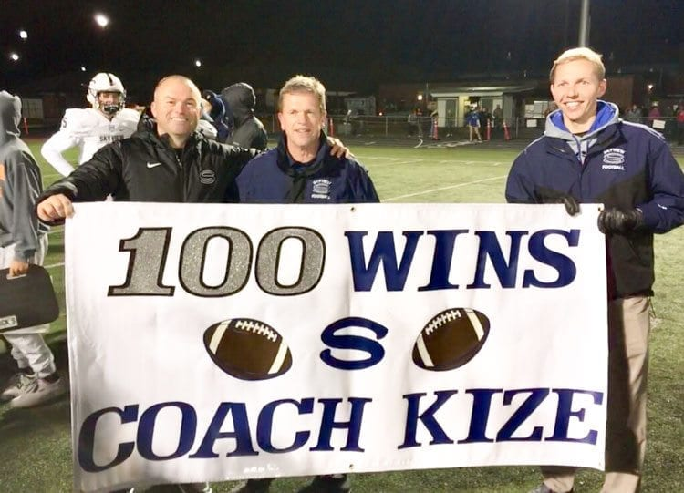 The Skyview administration celebrated football coach Steve Kizer's 100th victory with the Storm after last week's win. Principal Jim Gray, left, and athletic director Luke LeCount, right, unveiled this sign for Kizer (middle) on the field after the game. Photo courtesy Jim Gray.