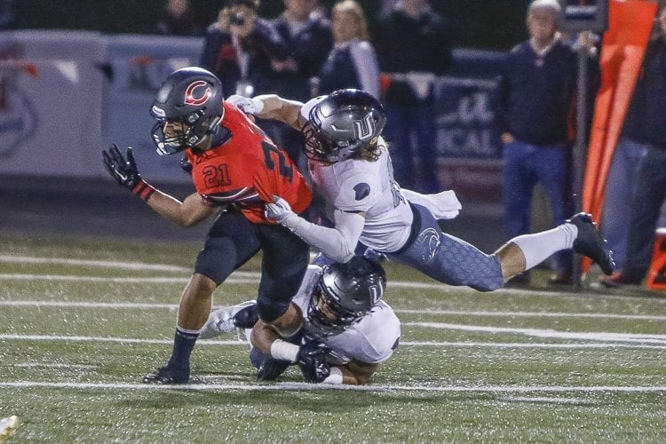 Union defender Tiernan Stanley (25) tackles Camas wide receiver Drake Owen (21) during Friday's game at Doc Harris Stadium in Camas. Photo by Mike Schultz