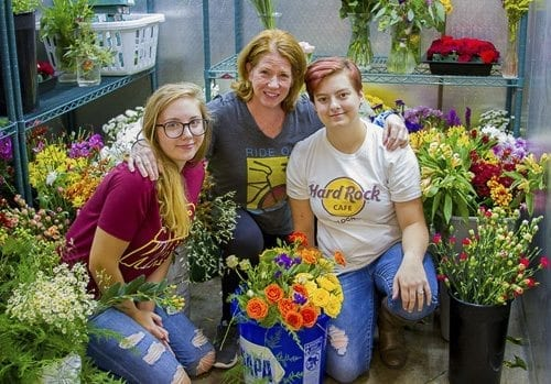 Kylee Jones, junior (left), Mary Ellen Vetter, teacher (center), and Jennifer Parkhill, senior (right), appreciate the variety of hands-on skills floral design offers that are applicable to employment in virtually any job industry. Photo courtesy of Woodland Public Schools