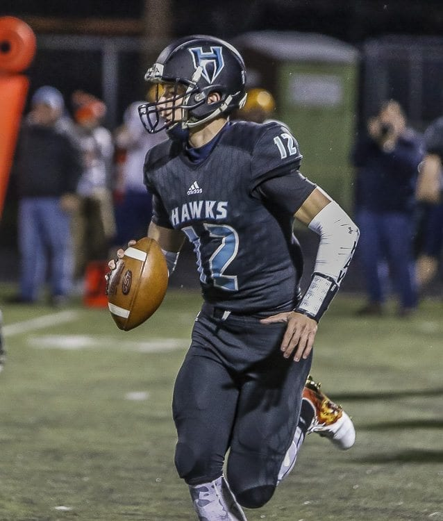 Hockinson quarterback Canon Racanelli (12) threw six touchdown passes to lead the Hawks to a 49-8 victory over Aberdeen Friday in a state qualifier playoff game at District Stadium in Battle Ground. Photo by Mike Schultz