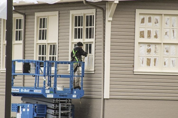 A worker conducts paint repairs on a window on the motor repair shop at the East Vancouver Barracks as part of a six-month project to repaint five buildings on the site. Photo by Alex Peru