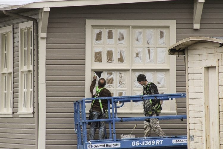 Workers remove masking material from a window in the former US Army motor repair shop as part of an ongoing effort to preserve structures at the East Vancouver Barracks. Photo by Alex Peru.
