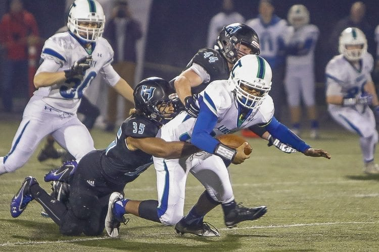 Hockinson linebackers Tony Richardson (35) and Colton Wheeler (44) join together to bring down a Liberty ball carrier in Saturday's state quarterfinal playoff game at District Stadium in Battle Ground. Photo by Mike Schultz