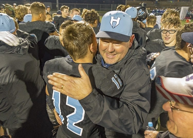 Hockinson quarterback Canon Racanelli (12) embraces his father Josh Racanelli, one of the team's assistant coaches, after the Hawks earned a trip to the Class 2A state semifinals with a victory over Liberty Saturday. Photo by Mike Schultz