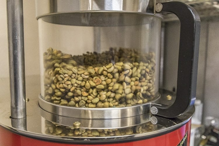 Green coffee beans are roasted in the roasting machine to a predetermined roasting profile set by Matthew Selivanow. Photo by Mike Schultz