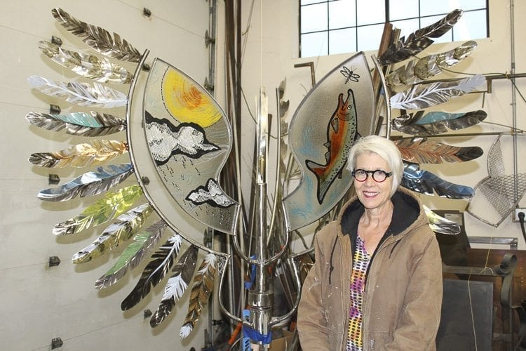"""Vancouver artist Sharon Warman Agnor stands by a portion of the sculpture """"Wings of the World"""" in her shop before it was installed at Overlook Park in Ridgefield. Photo by Alex Peru"""