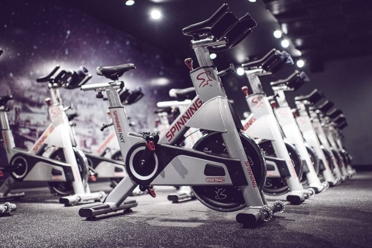 Each participant rides a stationary bicycle, and the studio is lit by candlelight during the workout sessions. Photo courtesy of StarCycle