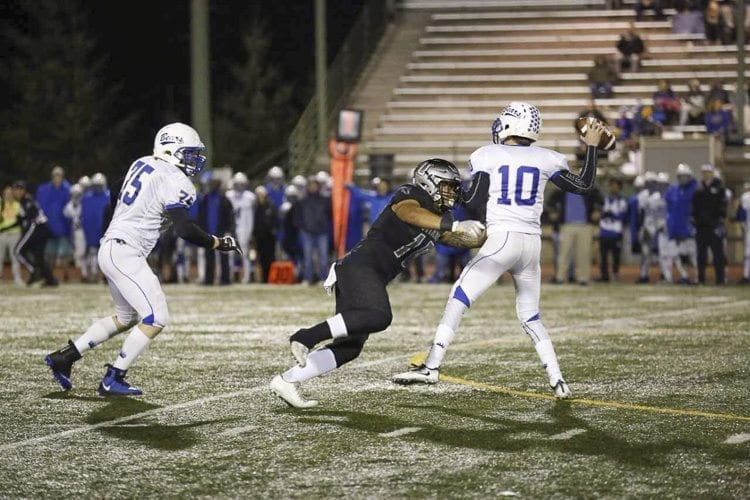 Union defensive lineman Zion Fa'aopega put the pressure on Tahoma quarterback Conner Lambro during their playoff game Friday at McKenzie Stadium. The Union defense held Tahoma to 97 yards in the first half, leading to a 41-14 victory. Photo by Heather Tianen