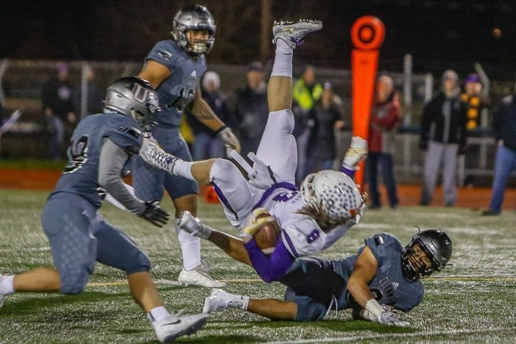 The Union defense upends Sumner running back Ben Wilson (8) during Friday's state playoff game at McKenzie Stadium. Photo by Mike Schultz