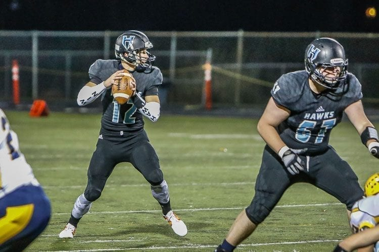 Hockinson quarterback Canon Racanelli (12) is shown here looking for an open receiver in a playoff win over Aberdeen. Providing protection is Hawks lineman Garrett Kondel (67). Racanelli will need time to throw in Saturday's Class 2A state championship game against Tumwater at the Tacoma Dome. Photo by Mike Schultz