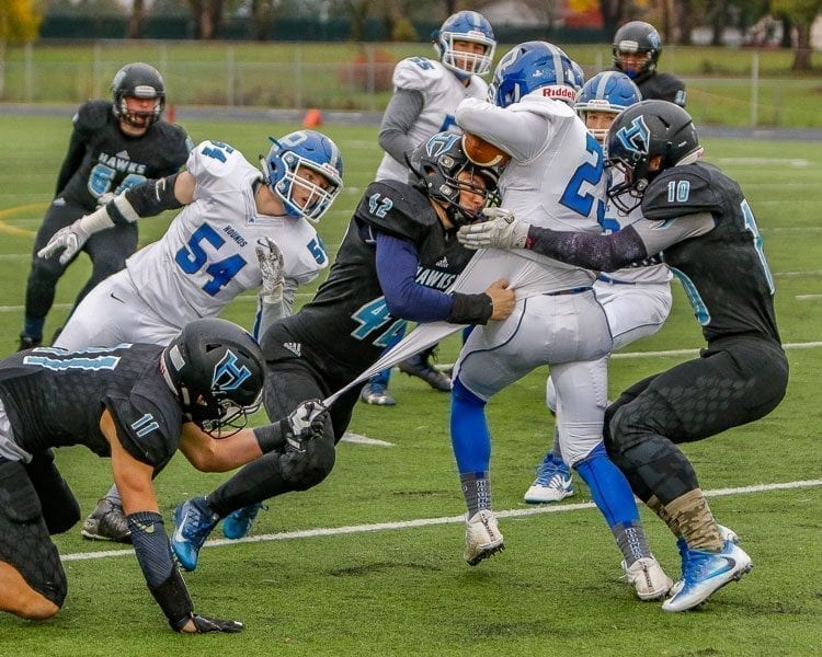 Hockinson's defense will have its toughest test of the season trying to stop Tumwater's disciplined, run-oriented offense in Saturday's Class 2A state championship game at the Tacoma Dome. Here, Hockinson defenders Sawyer Racanelli (11), Jonathon Domingos (42) and Kyle Brabec (10) stop a Pullman ball carrier in a previous playoff game. Photo by Mike Schultz