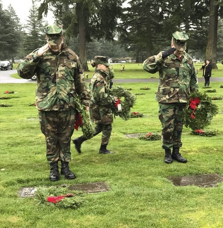 Young Marine Corporal Phillip Taylor (left) and Young Marine Lance Corporal Keelen Goldsworth pause to salute the graves of veterans while placing wreaths at Evergreen Memorial Gardens during the Wreaths Across America ceremony. Photo courtesy of Lewis and Clark Young Marines