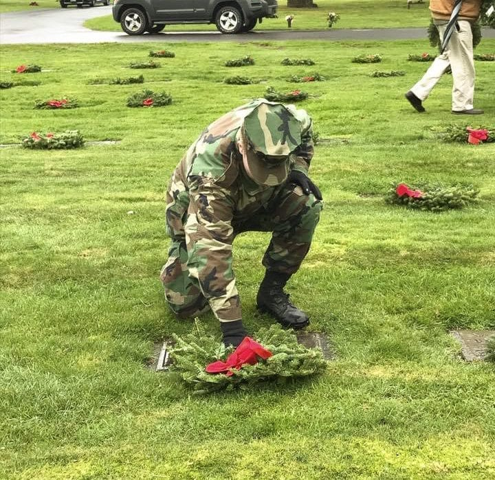 Young Marine Lance Corporal Keelen Goldsworth places a wreath on a veteran's grave at Evergreen Memorial Gardens for the Wreaths Across America Ceremony. Photo courtesy of Lewis and Clark Young Marines
