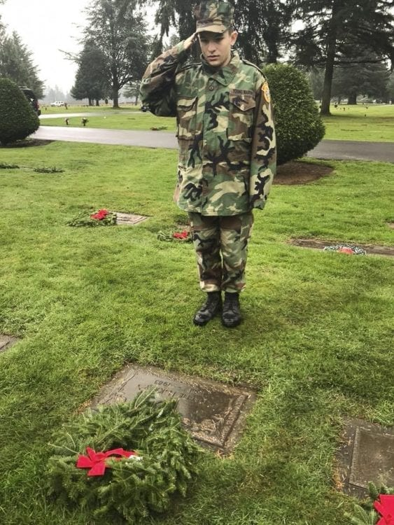 Young Marine Private Victor Wright salutes a veteran's grave after placing a wreath for the Wreaths Across America ceremony at Evergreen Memorial Gardens. Photo courtesy of Lewis and Clark Young Marines