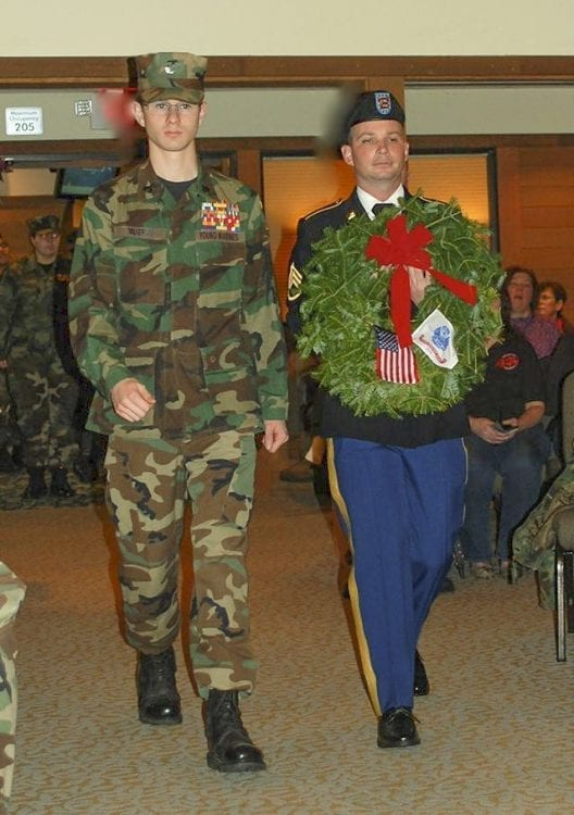 During the Wreaths Across America ceremony at the chapel of Evergreen Memorial Gardens, a wreath was brought in to represent each branch of the military, as well as the Merchant Marine and POW/MIA. Young Marine Sergeant Sean Murray escorts Army representative Staff Sergeant (retired) Patrick Vernier into the chapel. Photo courtesy of Lewis and Clark Young Marines