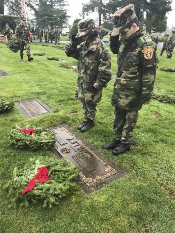 During the Wreaths Across America ceremony at Evergreen Memorial Gardens, Young Marines read the name of each veteran they placed a wreath for, and stood to salute the graves. Photo courtesy of Lewis and Clark Young Marines