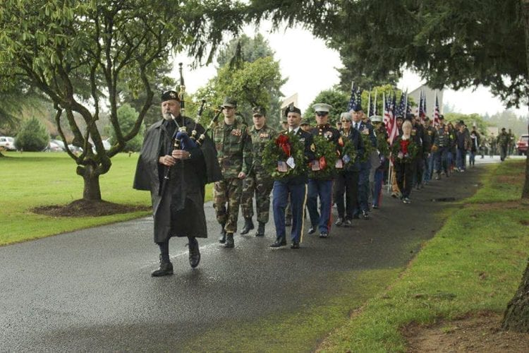 Portland Police Highland Guard member Garth Edwards on bagpipes leads a procession from the Evergreen Memorial Gardens chapel to the cemetery to begin placing wreaths on veterans' graves as part of the Wreaths Across America ceremony. Photo courtesy of Lewis and Clark Young Marines