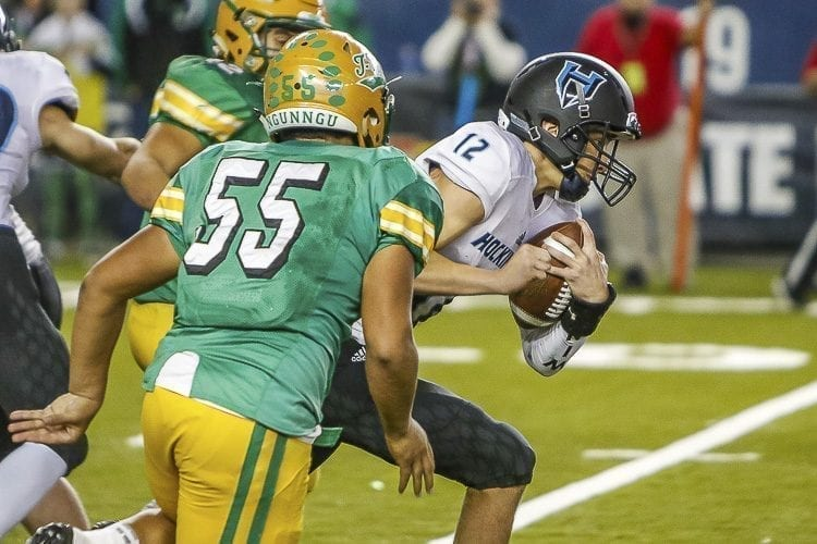 Hockinson quarterback Canon Racanelli (12) rushes for some of his 65 yards Saturday in the Class 2A state football championship game with Tumwater. Racanelli also had 316 yards passing and three touchdowns to lead the Hawks to the state championship. Photo by Mike Schultz