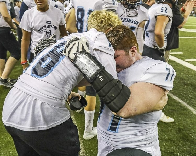 Hockinson linemen Nathan Balderas (71) and Liam Heinl (78) share a hug as the clock winds down in the Hawks' state championship victory over Tumwater Saturday in the Tacoma Dome. Photo by Mike Schultz