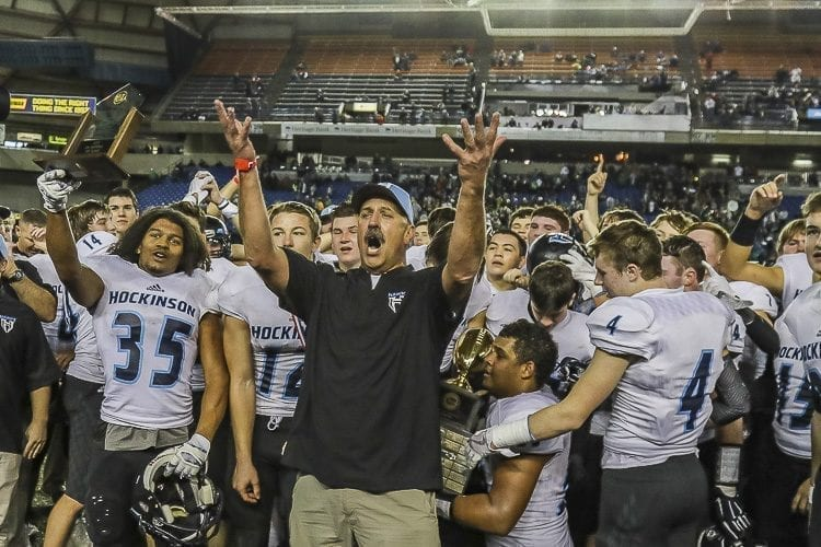 Hockinson coach Rick Steele (center) and his players celebrate with their fans in attendance at the Tacoma Dome Saturday. The Hawks defeated Tumwater 35-22 to claim the Class 2A state high school football championship. Photo by Mike Schultz