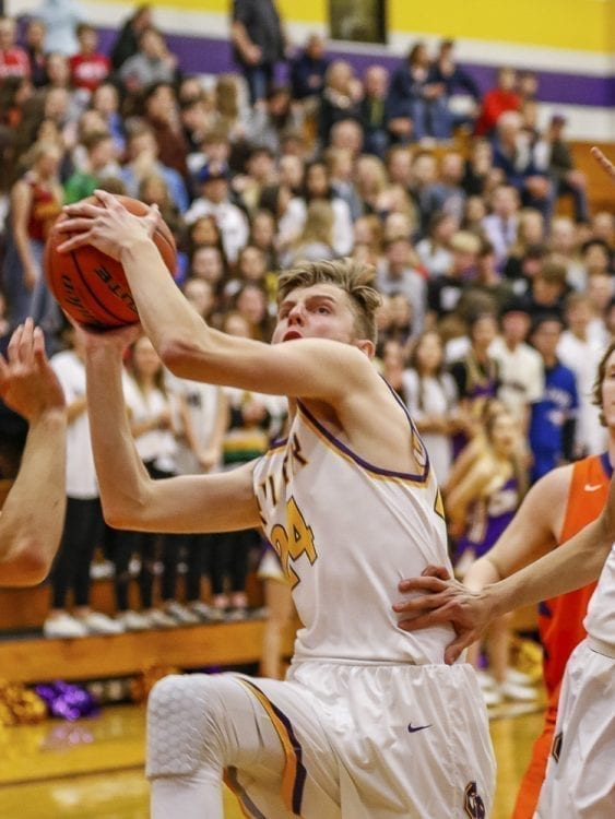 Columbia River's Jack Armstrong (24) goes strong to the basket against Ridgefield. Armstrong scored his team's first six points and River never trailed in the team's 10th consecutive victory. Photo by Mike Schultz