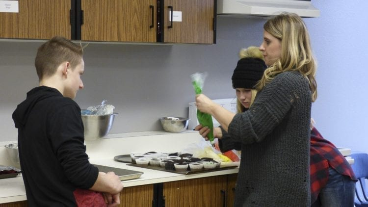 Ridgefield High School teacher Stefanie Foster (far right), assists Foods 1 students Austin Willis (left) and Alyssa Dewey as they prepare their entry for Cupcake Wars. Photo courtesy of Ridgefield School District