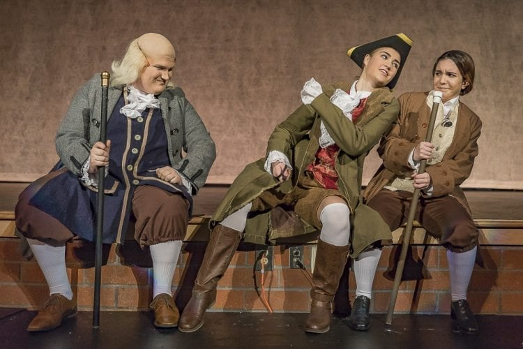"""Rowan Segura as John Adams (right) is not so sure of Richard Henry Lee's plan, as played by Natalie Williams. Ben Franklin, played by Jordyn Fields, seems to be OK with it during a scene of """"1776"""" by Heritage High School. Photo by Mike Schultz"""