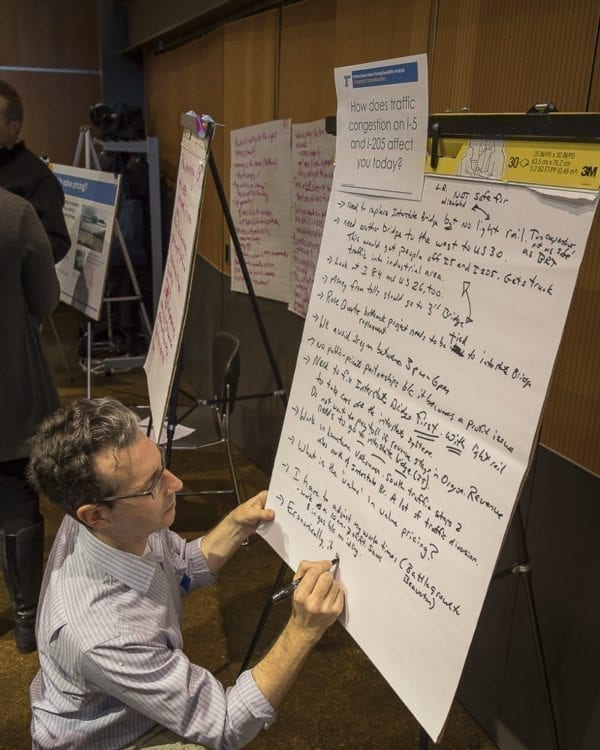 At the ODOT open house regarding tolls or value pricing, attendees could engage in dialogue by writing their concerns and experiences on easels provided for the public. Here, Value Pricing Senior Planner Mike Mason adds information to an informational easel. Photo by Mike Schultz
