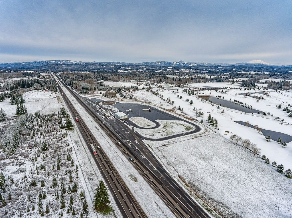 A snow cover that blanketed Clark County overnight was still intact Wednesday afternoon including near I-5 at the WSDOT weigh station near Ridgefield. Tri-Mountain Golf Course can be seen off to the east. Photo by Mike Schultz