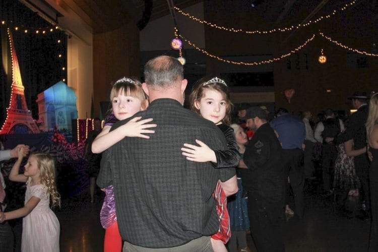 This father had his arms full Saturday at the 14th annual Woodland Father/Daughter Ball hosted by Grace Community Church at Woodland High School. Photo courtesy of Grace Community Church