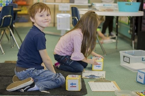 At one station, students toss blocks with different words and then select a word that rhymes with the one on their block. Photo courtesy of Woodland School District